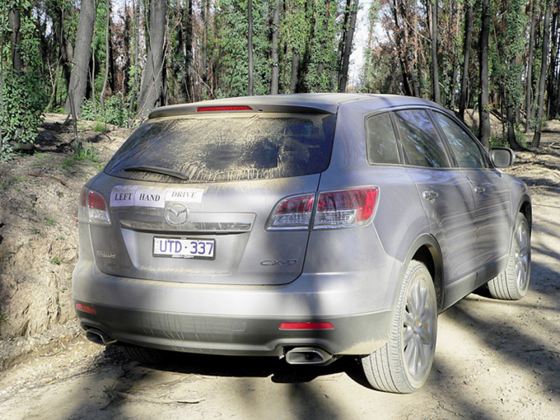 Rear view of Silver 2007 Mazda CX9 driving down unsealed road in the bush
