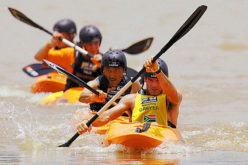 4 men wearing helmets in orange kayaks racing in the Land Rover G4 Challenge