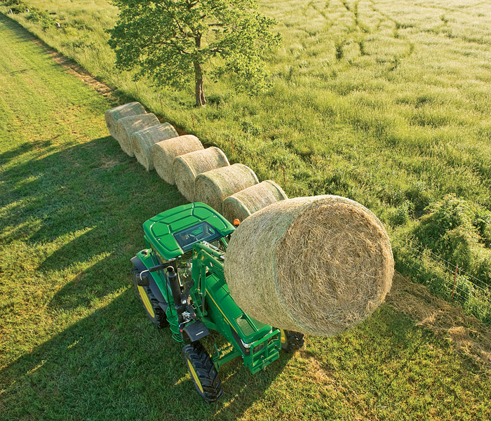 John Deere 6 Series tractor lifting a hay bale