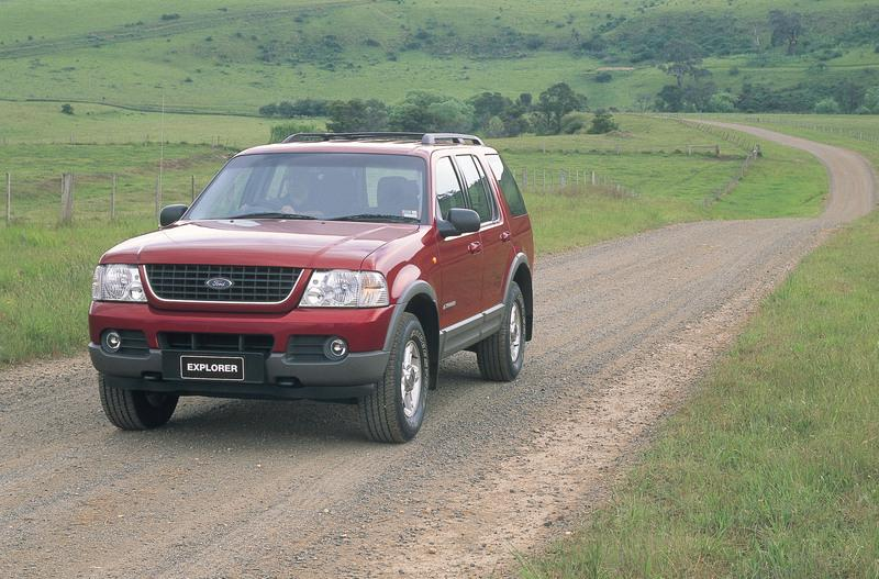 Red 2001 Ford Explorer on unsealed country road