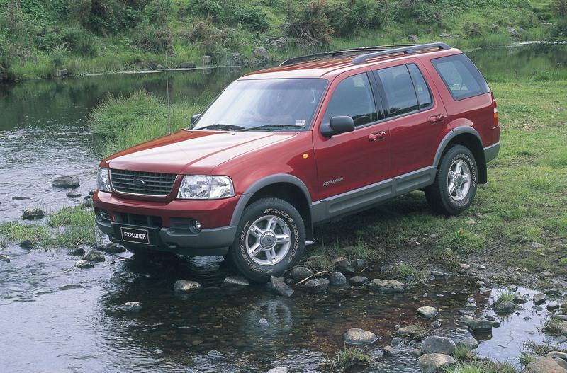 Red 2001 Ford Explorer entering a stream