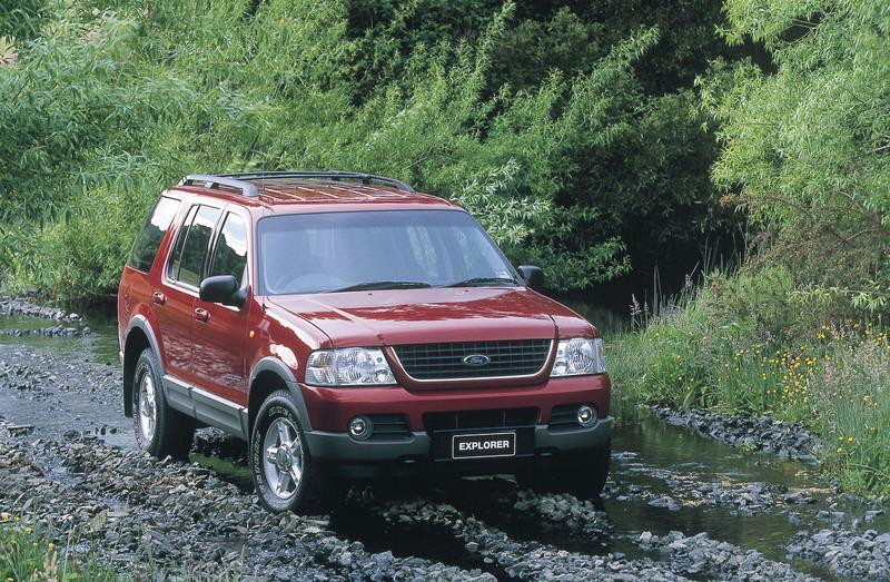 Red 2001 Ford Explorer on muddy track